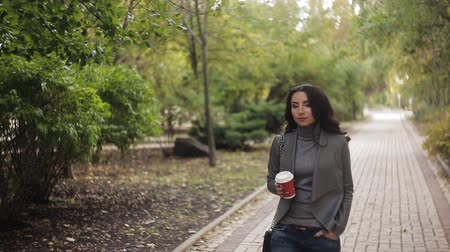 pulóver : beautiful girl is drinking coffee in the park. Autumn soft light Stock mozgókép