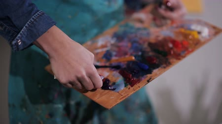 expressionism : artist squeezes out a tube of paint on the palette. close-up