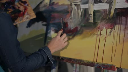 pallette : A woman artist works on a painting palette knife and oil paints