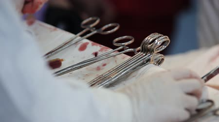 instrumentos : surgical instruments contaminated with blood on the table in the operating room. close-up