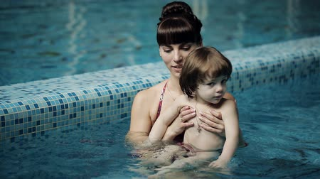 мама : Mom teaches a child to swim in the pool. Mom and son swimming in the pool