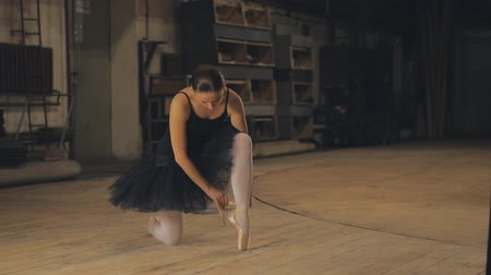 teljesít : Ballerina tying pointe ballet shoes on stage.