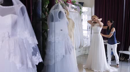 подвенечное платье : women choosing wedding dress in shop. she is not completely