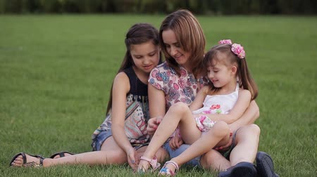 matka dziecko : happy family outdoors on the grass in a park. mom and two children smiling