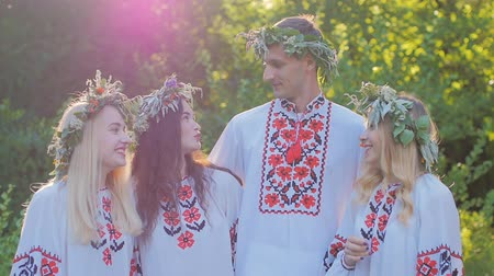equinox : a group of girls and boys in the Slavic national dress in the woods smiling and talking. The celebration of the summer equinox.