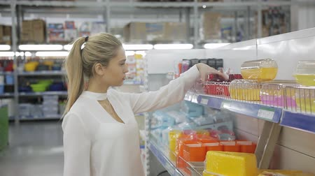 mutfak malzemesi : Young woman chooses kitchen utensils in the supermarket
