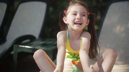 капелька : A little girl in a bathing suit is sitting on a lounger by the pool and laughing.