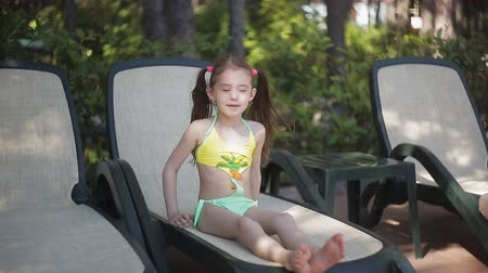 капелька : A little girl in a yellow bathing suit is basking in the sun sitting on a sunbed.