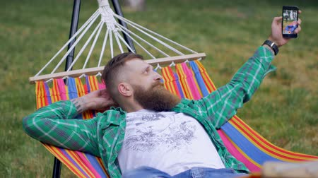 борода : A brutal man with a beard lies on a hammock in the nature and makes selfie on the phone