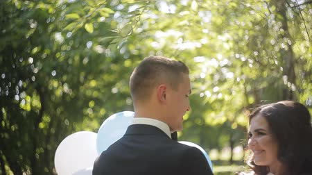 realizing : Happy newlywed bride and groom kissing, realizing that they are married now. Outdoor shot with summer park as background Stock Footage