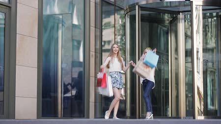 zsák : Happy women coming out of shopping mall with bags