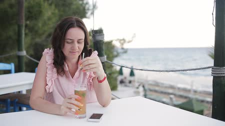 saman : Woman sitting in cafe with ice cocktail with sky and sea background.