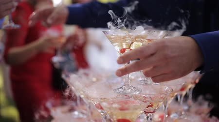 pour out : The guests hands take glasses with bubbling wine at the party. Glasses are built in the pyramids. No recognizable persons