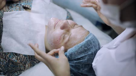 arcszín : a young girl receives treatment for acne. medical mask on face with problem skin Stock mozgókép