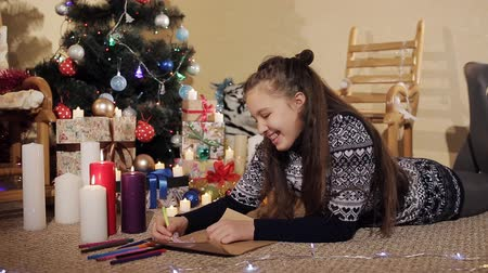święta : Teen girl is lying near decorated christmas tree and writing christmas letter to Santa Claus Wideo