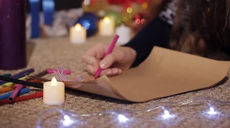 święta : cute teen girl lies near Christmas tree and writes letter to Santa Claus. Close-up Wideo