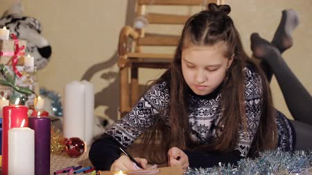 święta : Beautiful girl writes a letter to Santa Claus. A girl with long hair lay on the floor and wrote a letter to Santa Claus. Background with christmas presents.