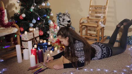 święta : nice little girl with long hair on the background of Christmas gifts and lit candles wrote a letter to Santa Claus