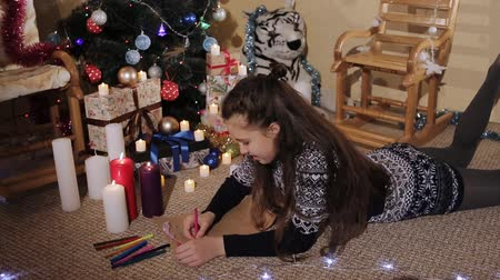 dát : brunette girl with long hair near a Christmas tree writing a letter. Dostupné videozáznamy