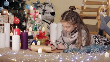 święta : cute little girl with long hair draws a postcard for Santa Claus. The baby is writing a Christmas letter Wideo