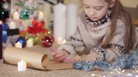 święta : A pretty little girl draws a drawing for Santa Claus near a beautifully decorated Christmas tree. Close-up. Handles of the little girl draw a picture Wideo