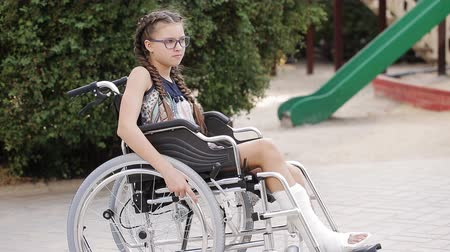 специальный : A girl with a broken leg sits in a wheelchair in front of the playground.