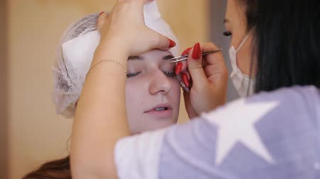 plucks : Master plucks the eyebrow of the girl with tweezers close-up Stock Footage