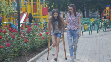 kule : Mom helps my daughter with a broken leg on crutches to walk along the street