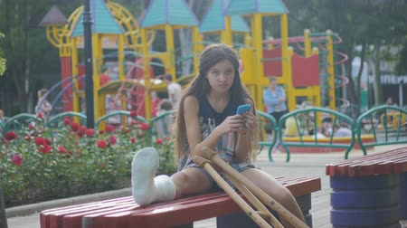 kule : Girl with a broken leg sits on a bench, on the background of a descriptive pad and looks at the smartphone Wideo