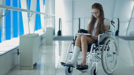 специальный : A young girl in a wheelchair is reading a book. Patient in a wheelchair in the hospital corridor.