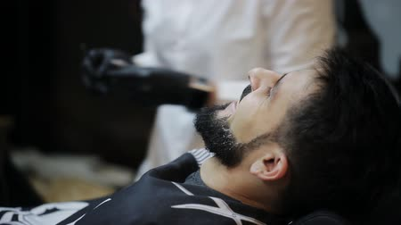 beard trimming : Shaving process of beards in Barbershop. Master makes a haircut beard client with vintage straight razor. Stock Footage