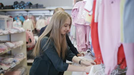 new clothes : Young happy pregnant woman choosing newborn clothes at the baby shop store stock footage video
