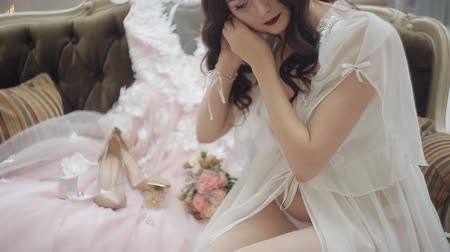 negligee : A young girl in lingerie and negligee sits on the couch and dresses pearl earrings