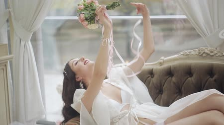 eleganckie : Wedding morning of the bride. A girl in her underwear and negligee admires her bouquet of roses