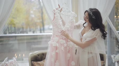 negligee : The bride in her underwear and negligee, standing by the window, enjoys the beauty of her wedding dress