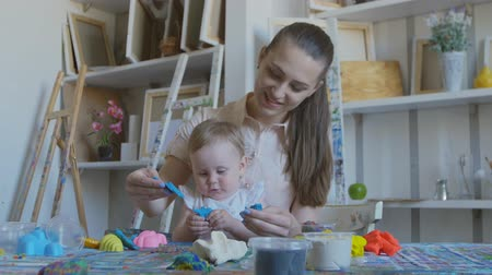plastelíny : A young attractive mother with her little child mixes different colors of plasticine. Preschool Development.