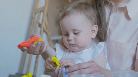 nanny : Close-up a young mother teaches her daughter to sculpt figurines from plasticine. Stock Footage