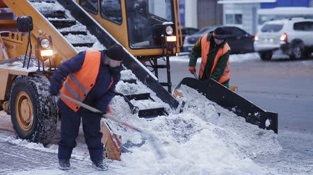 clearing away : municipal snow removal machine grabs snow from the street