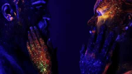 neskutečný : A man and a woman in the ultraviolet light caress each other. Fire and ice, two hypostases.