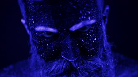 luxúria : A terrible bearded man in ultraviolet light. Close-up of a face.