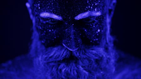 нереальный : A terrible bearded man in ultraviolet light. Close-up of a face.