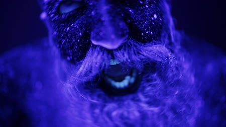 нереальный : An evil man with a beard in the ultraviolet light is frighteningly screaming. A terrible bearded man in ultraviolet light. Close-up of a face.