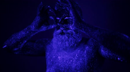bizarre : A terrible bearded man in ultraviolet light. Close-up of a face.