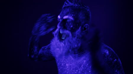 striptérka : An unreal dance of a man in the ultraviolet light. Strong, muscular man is a stripper. Dostupné videozáznamy