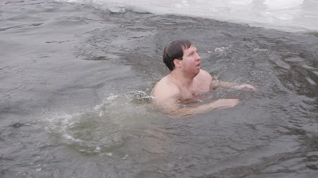 christening : Several Men are swimming in icy water in a river covered with ice. Hardening in a cold river. Healthy lifestyle