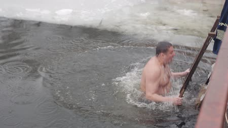 christening : A young guy dives into the icy water of a frozen river. Folk traditions. Healthy lifestyle. Winter hardening with ice water Stock Footage