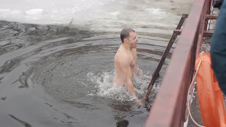 christening : The winter swimmer sinks into the ice water of the ice-hole. Hardening with ice water Stock Footage