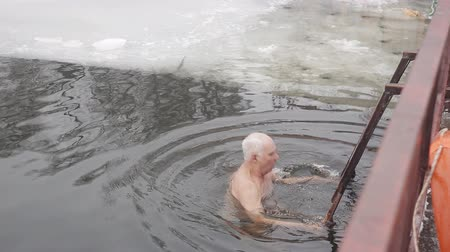 frozen lake : An elderly gray-haired man plunges into the ice water of an ice-hole. Hardening with ice water