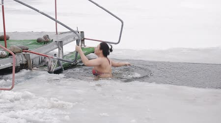 christening : A young girl is immersed in an ice hole. Hardening and swimming in a cold river. Healthy lifestyle
