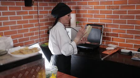gyro : Woman cook in a roadside restaurant prepares Shawarma. Woman chef puts the Shawarma on the grill and sear